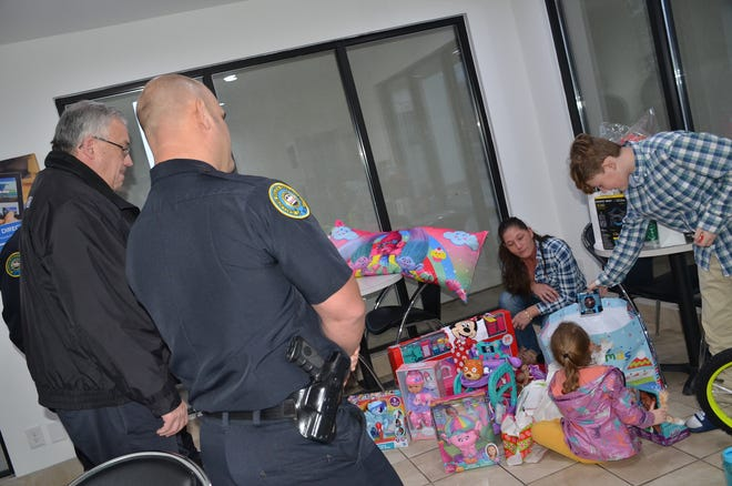 Gallatin police watch Lindsey Davis and her children, Konnor and Michaela, open Christmas presents the department gave the family. The White House family lost everything in a fire earlier in December.