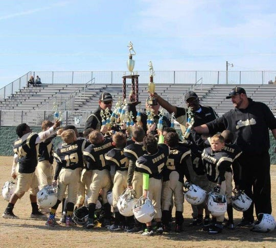 The 5-7 Division Springfield championship team celebrates on the field after winning the Super Bowl game.
