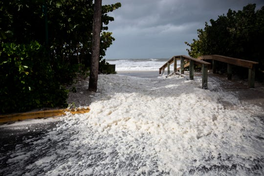 Strong winds blow sea foam out onto the road on Friday, Dec. 21, 2018, in Port Royal.