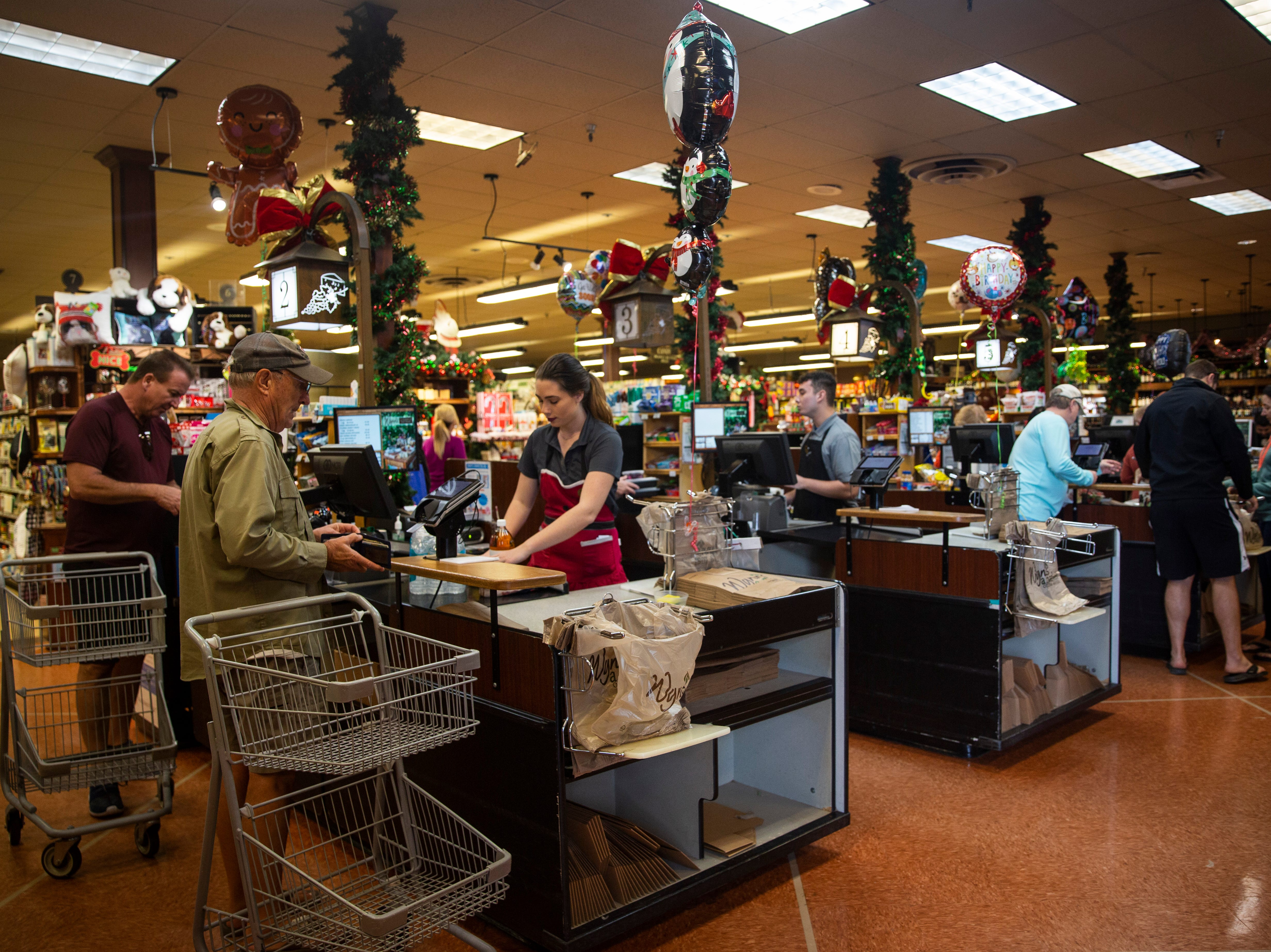 Customers check out after shopping on Friday, Dec. 21, 2018, at Wynn's Market in Naples. Wynn's Market is celebrating 80 years of business this year.
