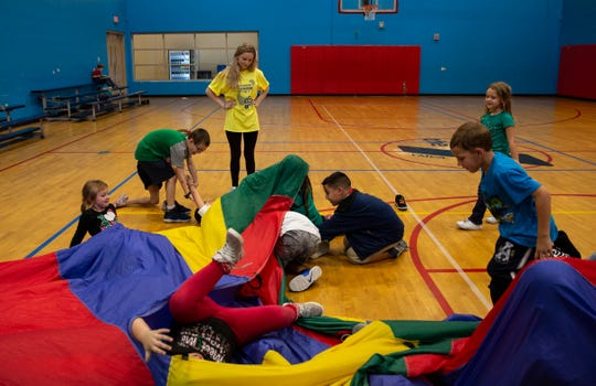 Children enrolled in the YMCA after school program in Bonita Springs play the sharks and lifeguard game while counselor, Brooke Horgan watches over them in the background at the gym on Wednesday, Dec. 19, 2018.