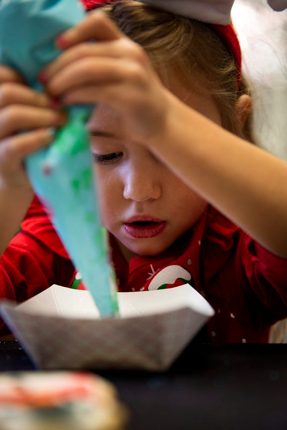 Emily Ashford, 4, concentrates on icing her cookie on Friday, December 21, 2018, at Angelic Desserts Bakery and Cafe in Naples.