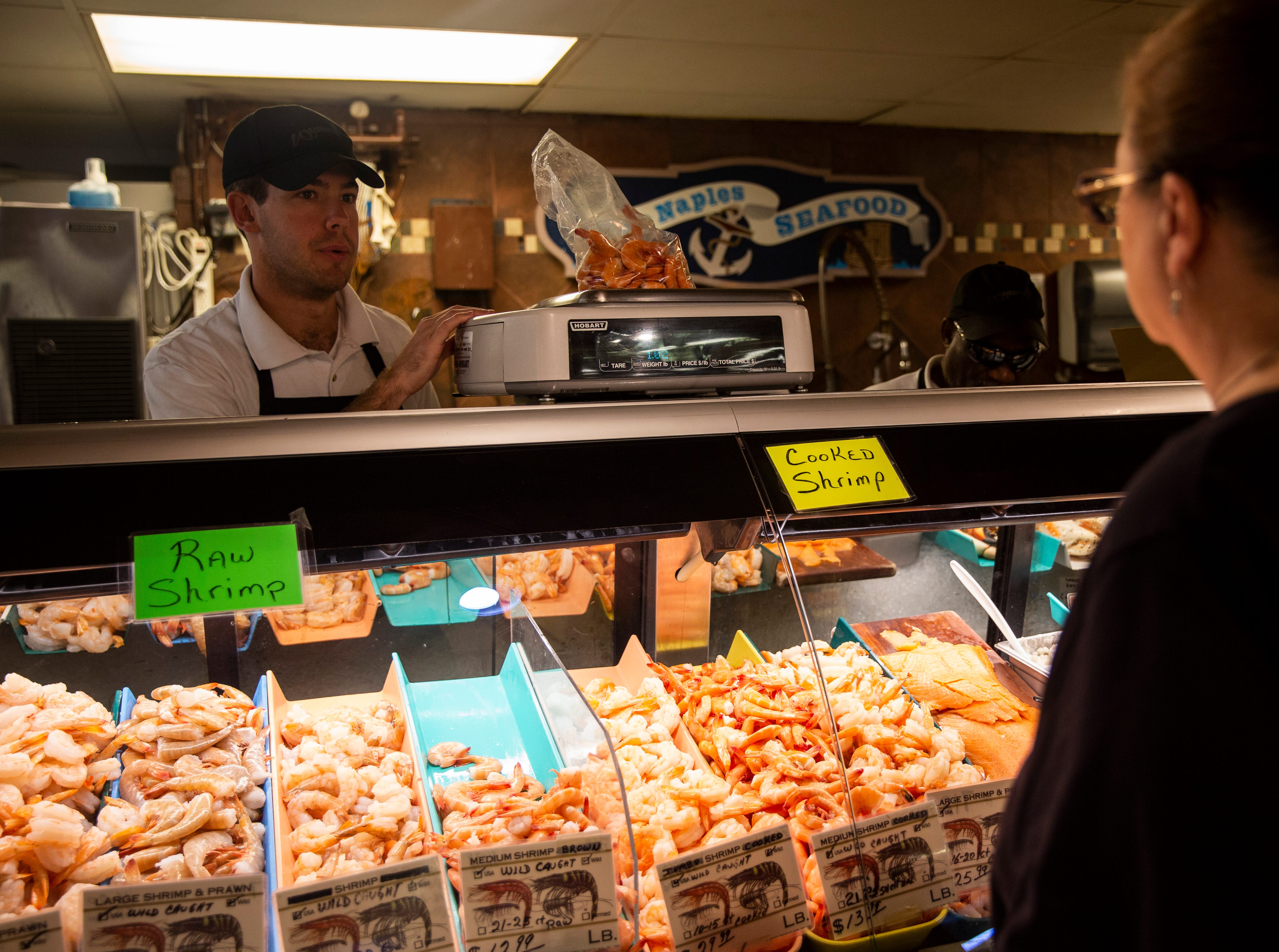 Larry Landberg helps a customer in the seafood department on Friday, Dec. 21, 2018, at Wynn's Market in Naples. Wynn's Market is celebrating 80 years of business this year.