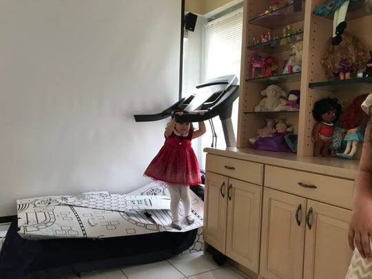 Isabella Soto, 2, plays peek-a-boo in her playroom at her Naples home in December 2018.