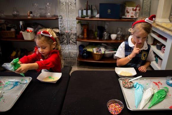 Mary Ashford, 6, right, contemplates her cookie decorating decisions while her sister Emily Ashford, 4, left, dives right in to icing on Friday, December 21, 2018, at Angelic Desserts Bakery and Cafe in Naples.
