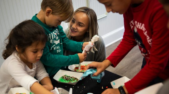 Cristina Droescher, center, talks to her son Levi Droescher, 4, as he decorates his cookie on Friday, December 21, 2018, at Angelic Desserts Bakery and Cafe in Naples.