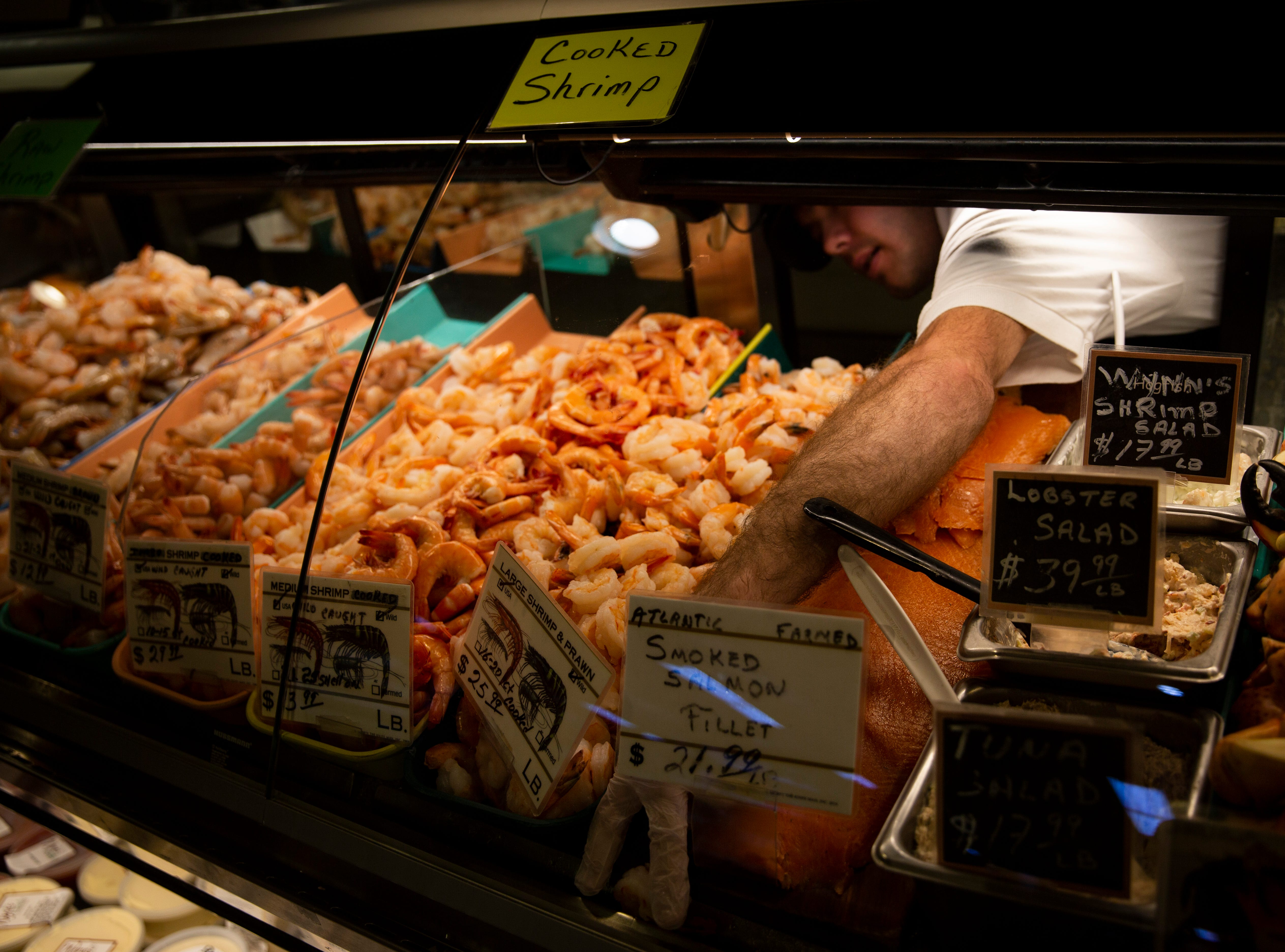 Larry Landberg works in the seafood department on Friday, Dec. 21, 2018, at Wynn's Market in Naples. Wynn's Market is celebrating 80 years of business this year.