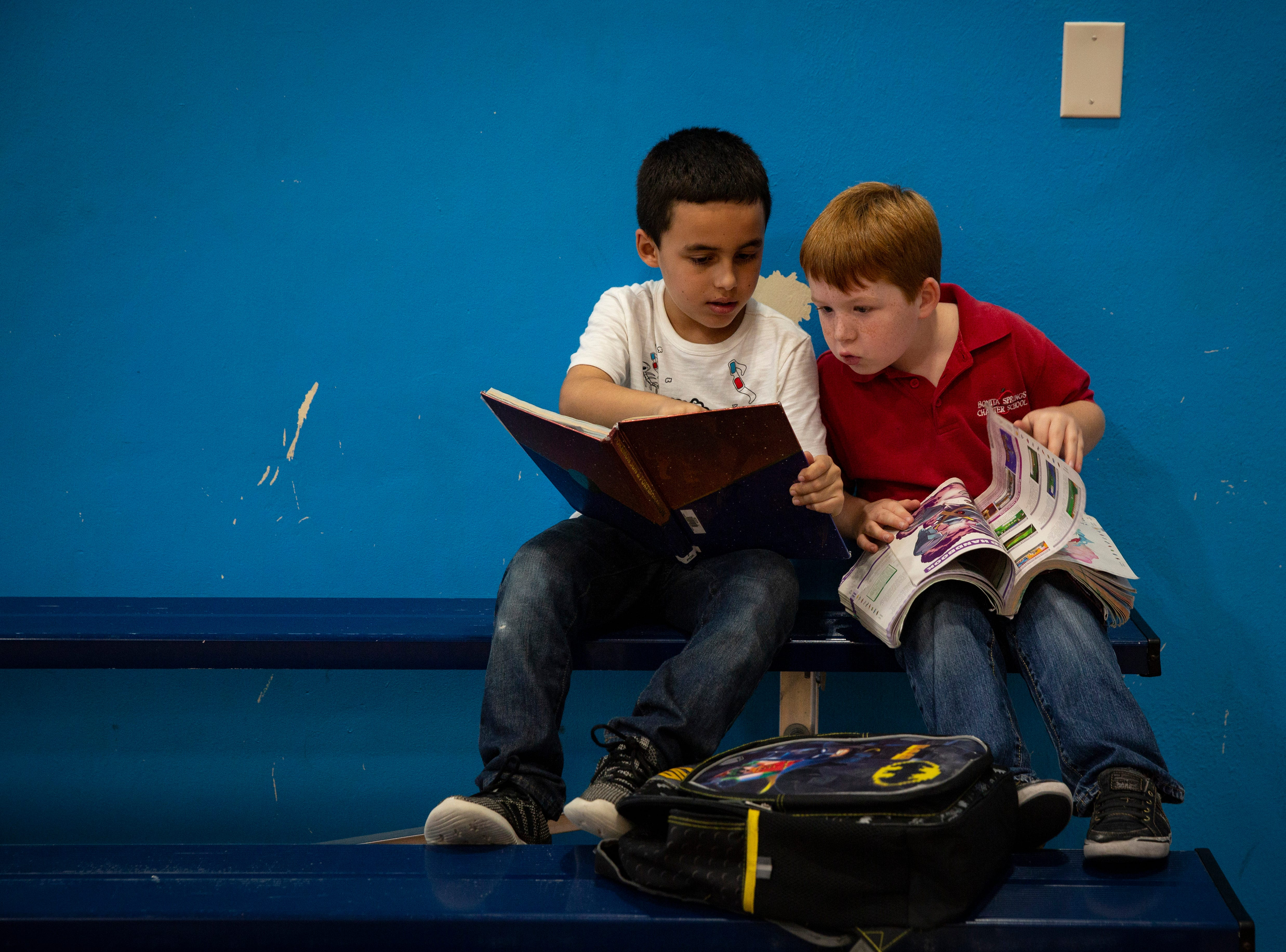 Julian Mejia, 7, left, and his friend, Dylan Wright, 7 sit by the gym bleachers reading and learning about Pokemon from books checked out of their school library, during the YMCA  after school program on Wednesday afternoon, Dec. 19, 2018, in Bonita Springs.