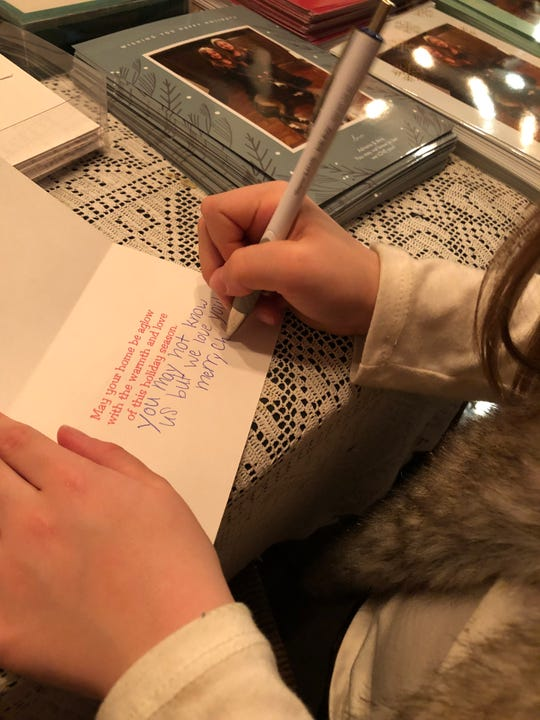 """Adriana Pollock, a third grader at Newton Elementary, is sending Christmas cards to about 2,000 people who are in nursing homes and foster care. In nearly 500 traditional cards, Adriana writes """"You may not know us but we love you."""""""