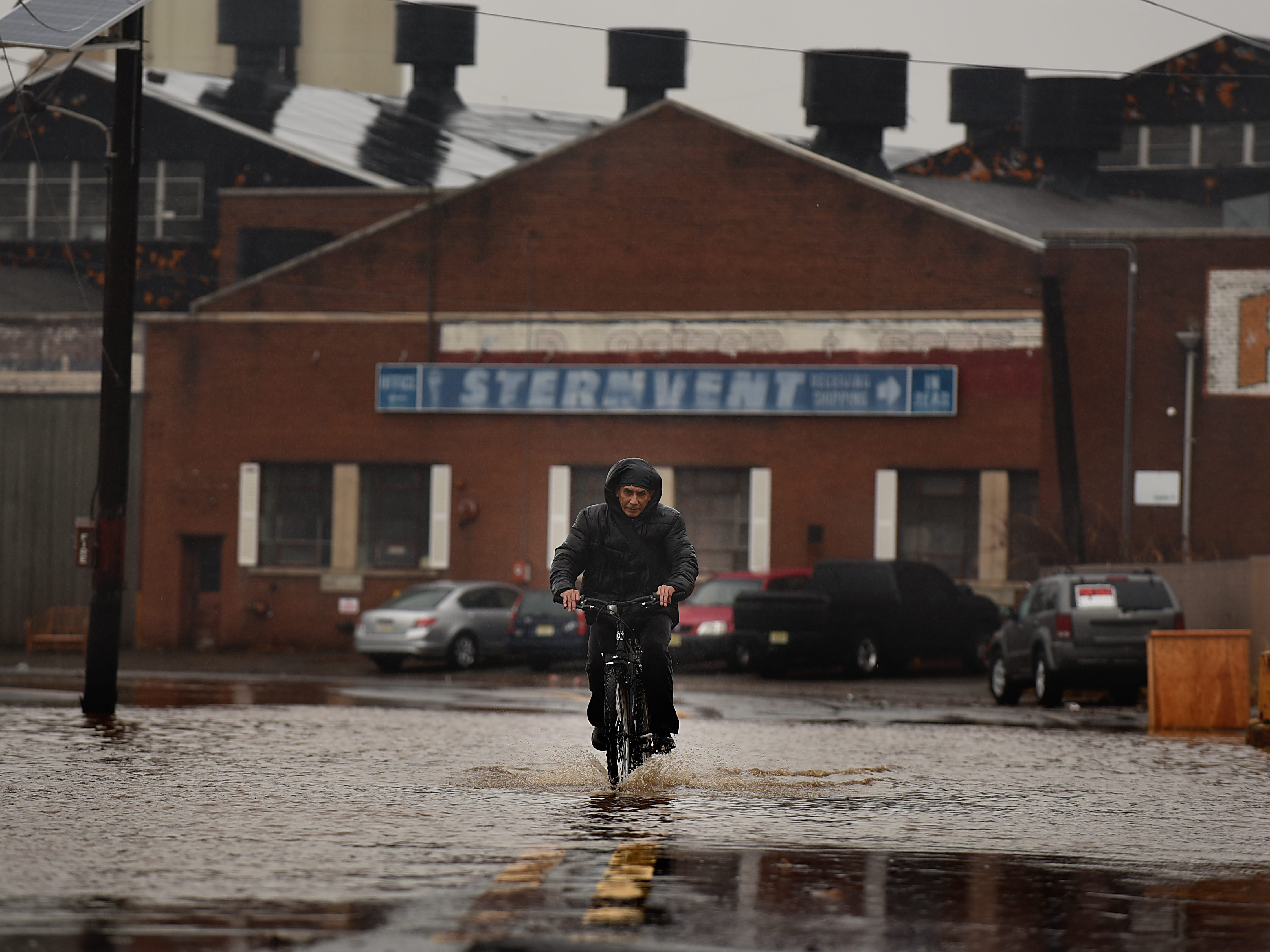 A man ride his bicycle along a flooded W. Fort Lee Road in Bogota on Friday December 21, 2018.