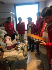 The Centennial boys basketball team distributed gifts on Thursday to children in the Pediatric Intensive Care Unit at Memorial Medical Center.