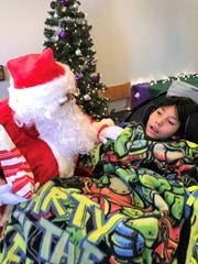 Santa speaks with Diage Kaydahzinne, a 4th-grader at Mescalero.
