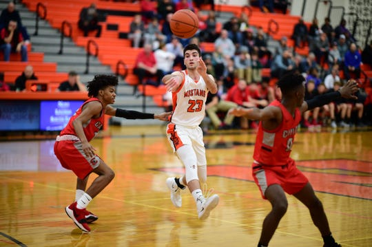 Northville's Daniel McLaughlin (23) fires off a pass between Canton defenders Kendall Perkins (left) and Vinson Sigmon (0).