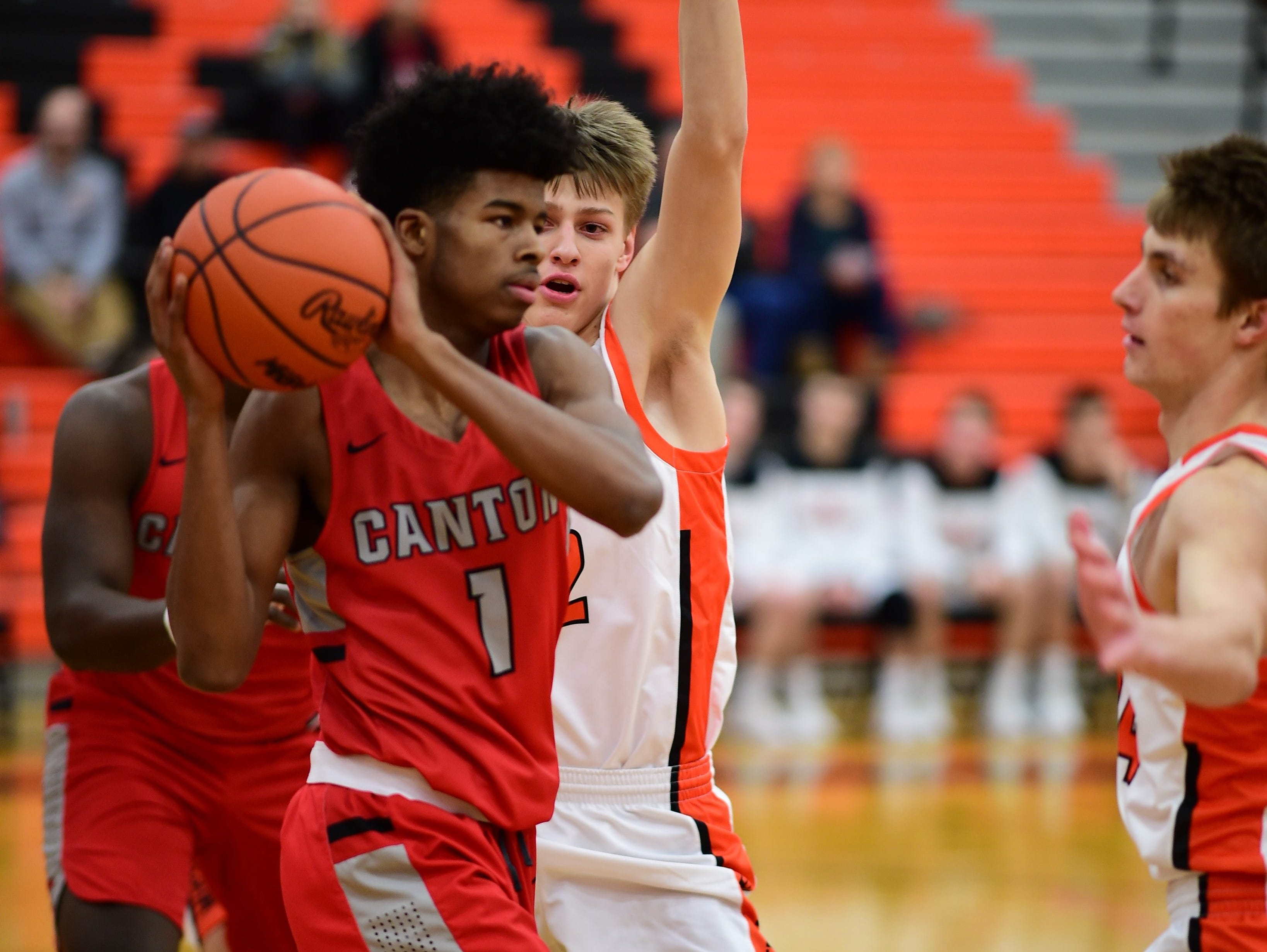Looking to find an open teammate is Canton's Kendall Perkins (1).
