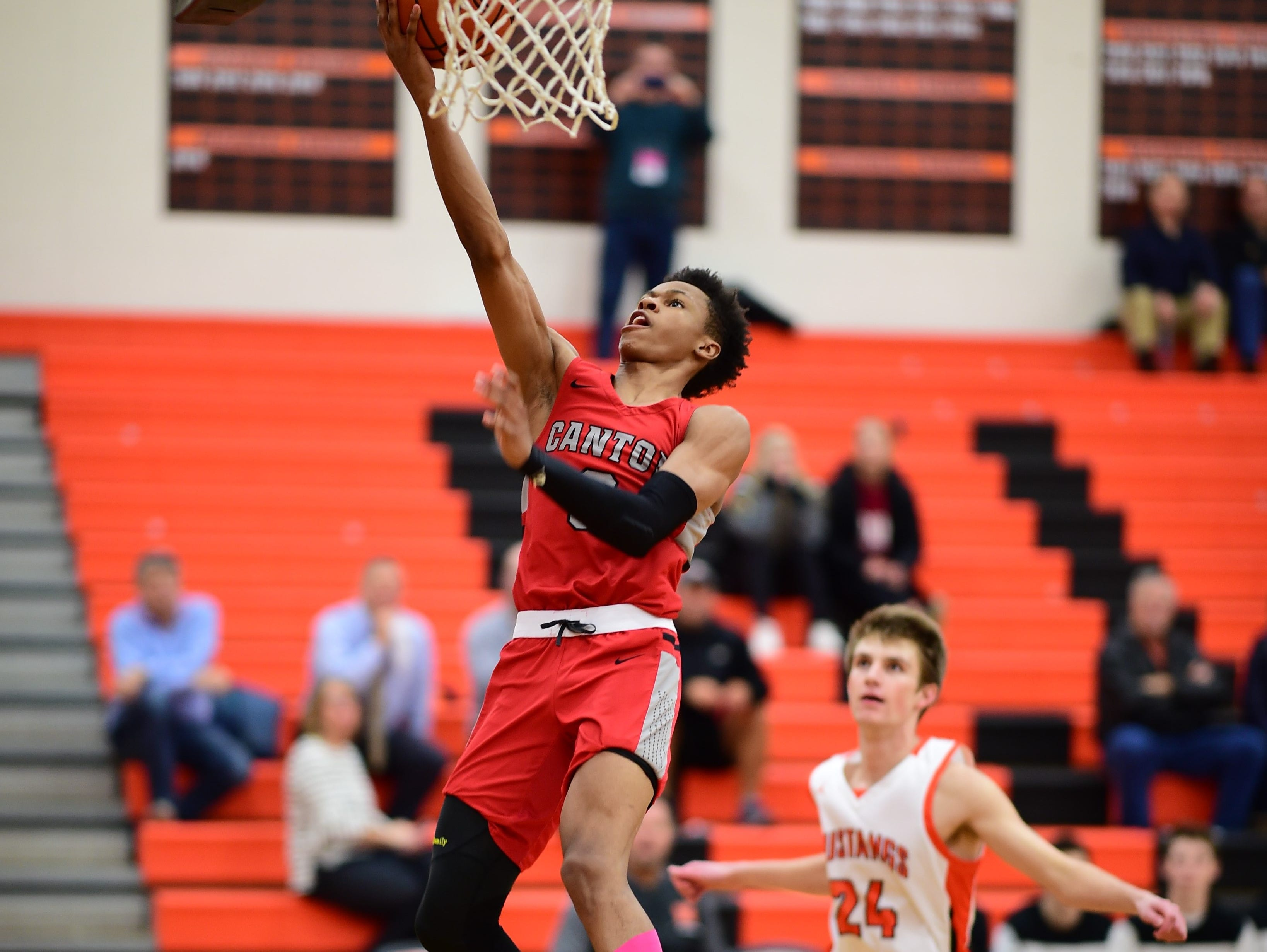 Going up for an early layup for the Canton Chiefs is senior guard B. Artis White. Trailing on the play is Northville's Steven Morrissey (24).