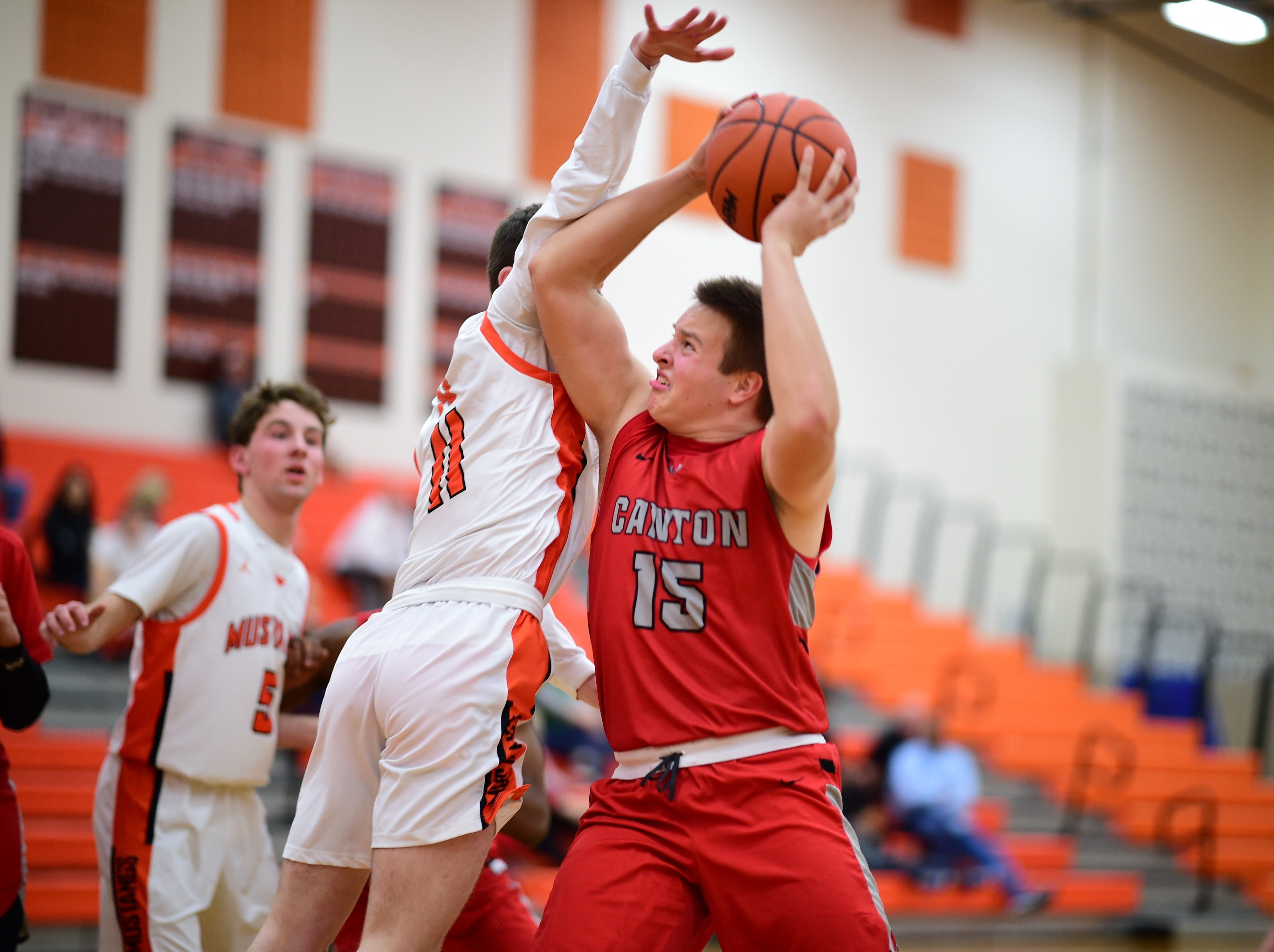 Muscling in for a shot is Canton's Max Barnes (15), while Northville's Tyler Milo (11) tries to deny the attempt.