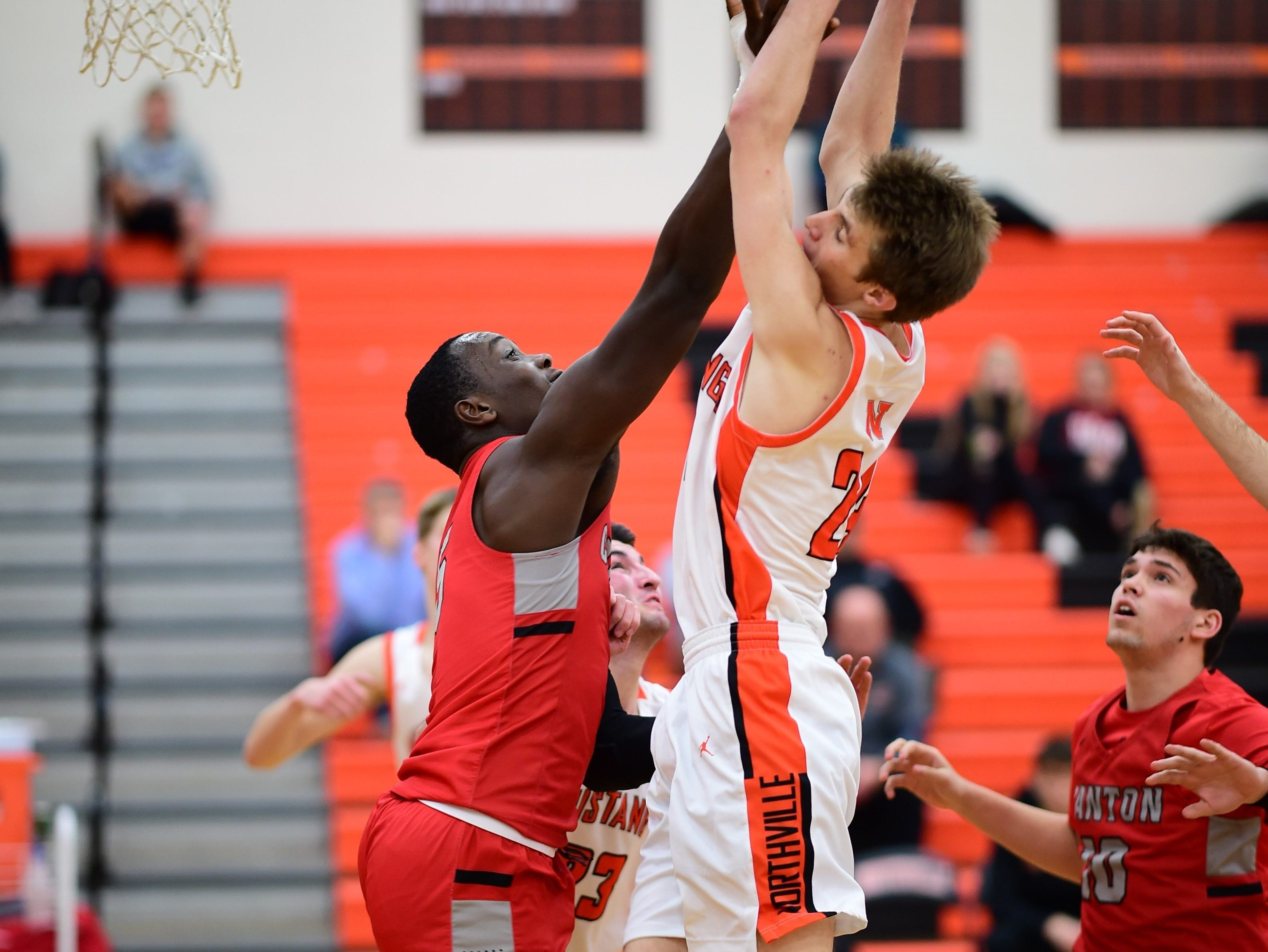 Canton senior big man Darius Robinson (left), who the previous day signed his national letter of intent to play Division I football at Missouri, shows some physicality on the basketball court against Northville.