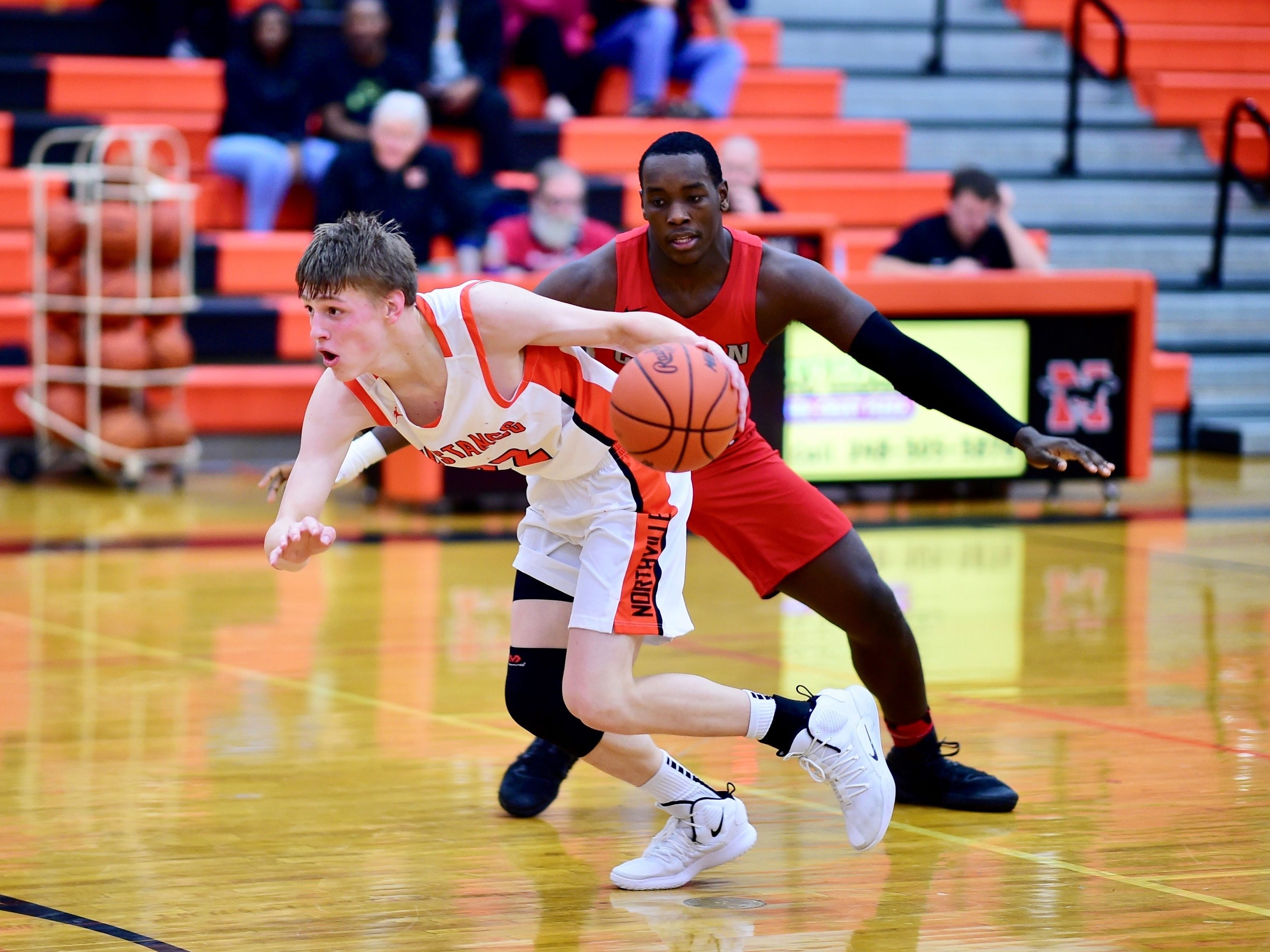 Northville's Ryan Pumper (22) tries to elude the tough defense of Canton's Darius Robinson during Thursday's game.