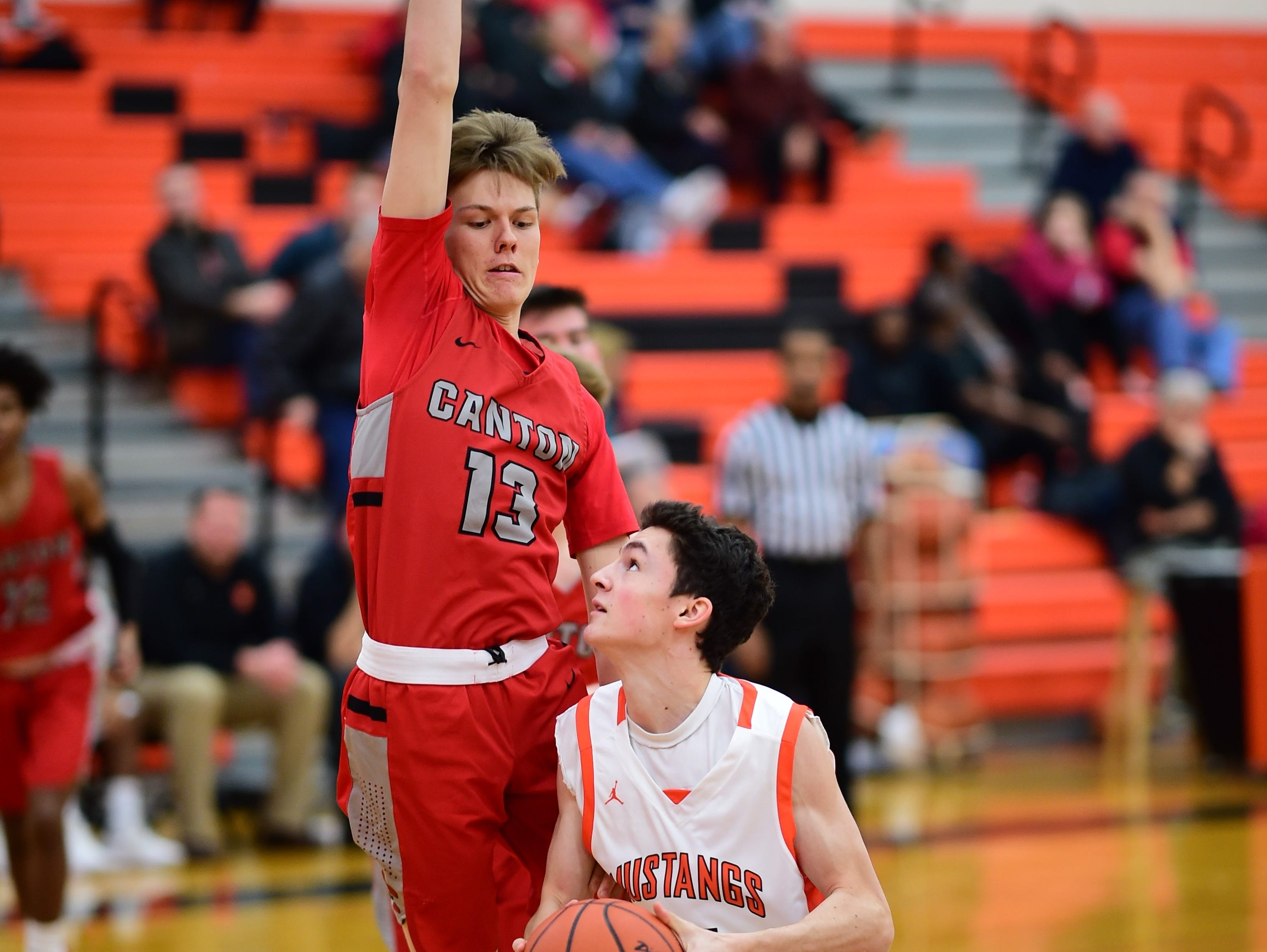 Canton's Jacob Rubis (13) defends against Northville's Max Barnes.