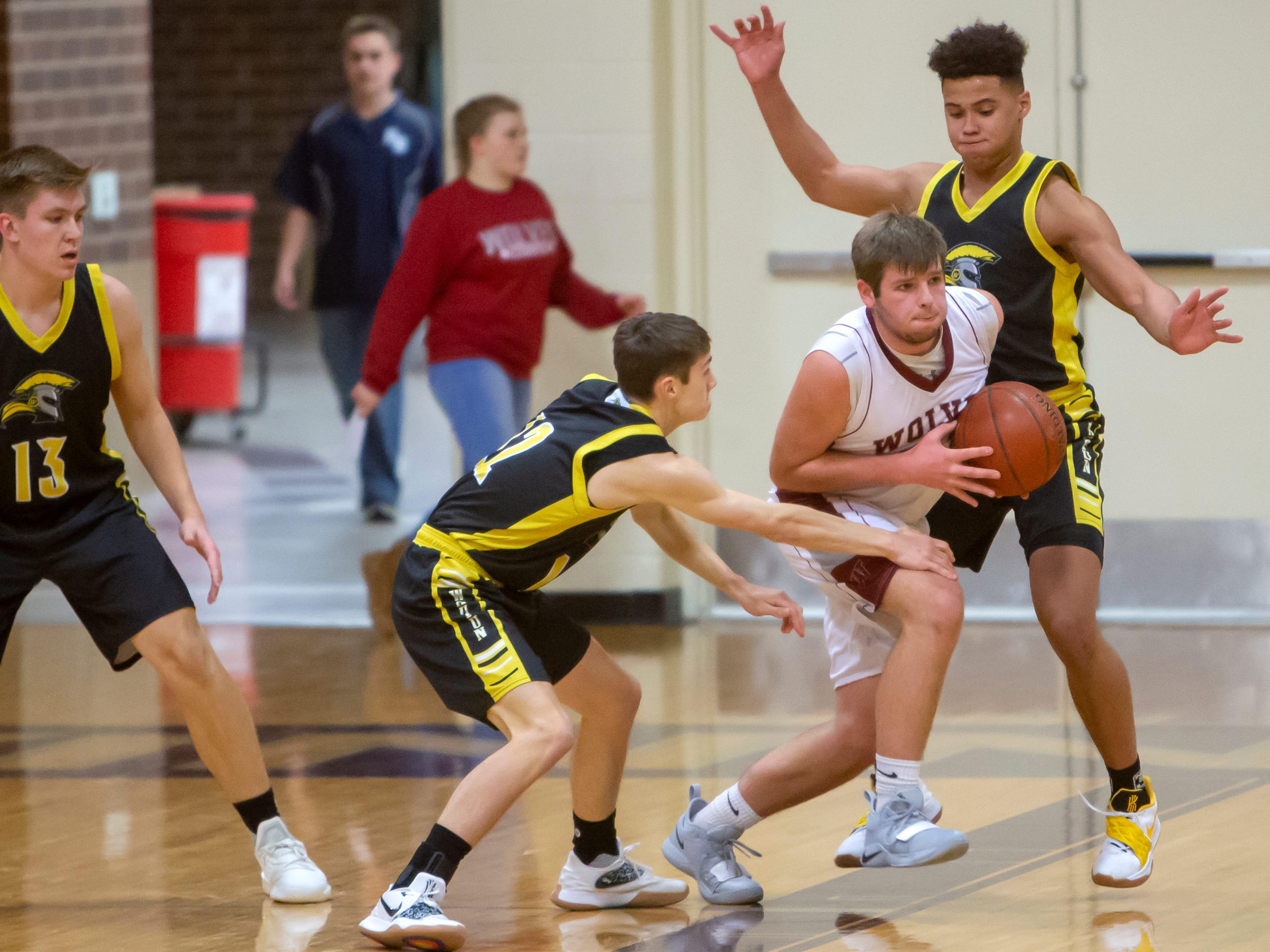 Winneconne's Andrew Jensen drives the ball between Waupun's Tyler Wiese and Quintin Winterfeldt at Winneconne High School on Thursday, Dec. 20, 2018.