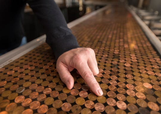 Owner Ed Riley points out the penny bar top that he personally made at the new Alcaniz Kitchen & Tap in downtown Pensacola.