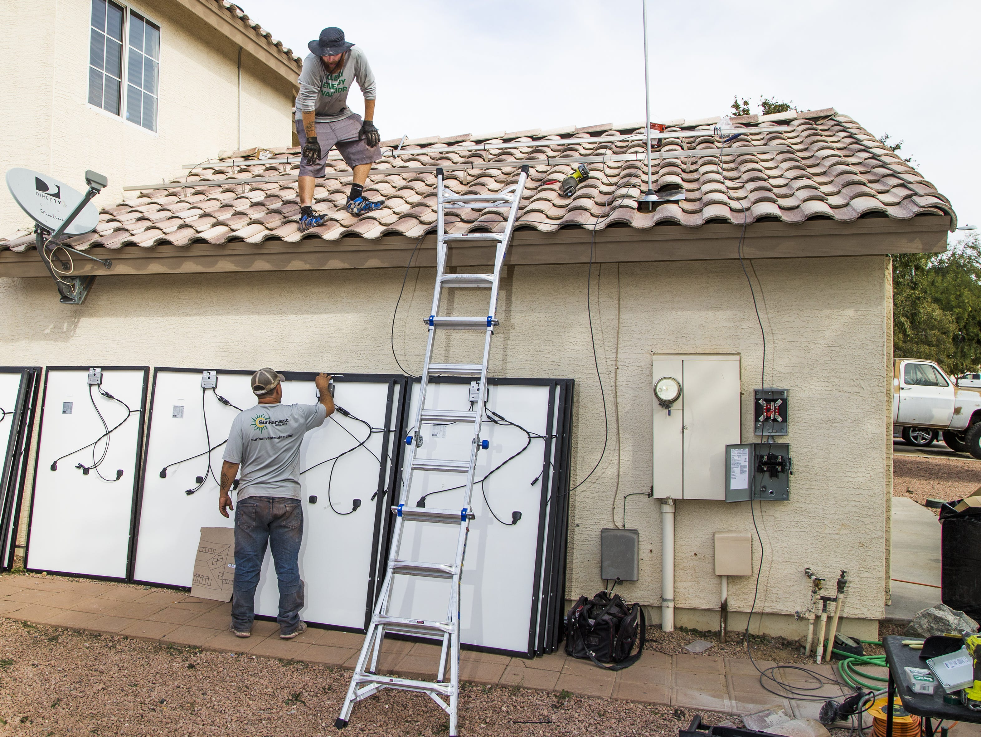 Larry Chambers (left) and Chris Miller, solar panel installers for SunHarvest Solar, install panels on a home in El Mirage on Nov. 20, 2018.