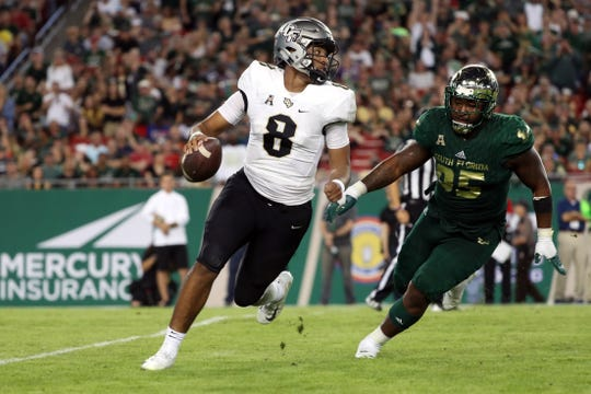 UCF quarterback Darriel Mack Jr. scrambles as South Florida defensive tackle Brandon Boyce brings pressure during the second half of a game at Raymond James Stadium.