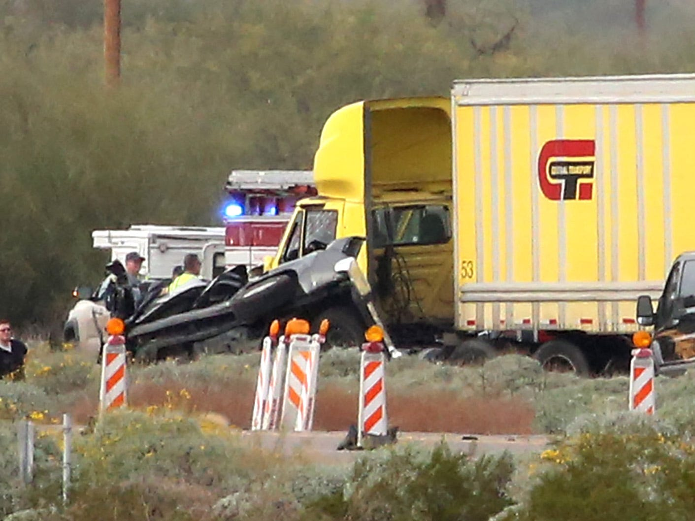 Investigators from the Arizona Department of Public Safety look over a vehicle and a tractor trailer on the scene of a multiple-fatality collision on Interstate 10 west of Pinal Airpark Road northwest of Tucson on Dec. 21, 2018.