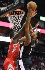 Trevor Ariza drives to the basket against Rockets center Clint Capela during the first half of a game on Dec. 19.