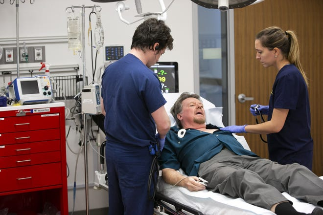 Dr. Jeff Tully and Dr. Rachel Helpling perform a medical simulation on actor Charlie Novotny, who is playing a patient  suffering from a hacked pacemaker, during the CyberMed Summit at the UA College of Medicine - Phoenix on Dec. 13, 2018.