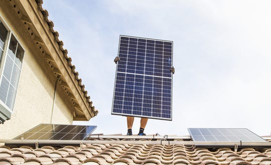 Chris Miller, a solar panel installer for SunHarvest Solar, installs panels on a home in El Mirage on Nov. 20, 2018.