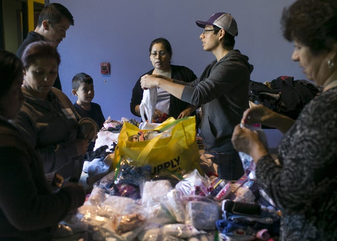 Asylum seekers and migrants from Central America wait at La Hermosa Church in Phoenix after being dropped off by U.S. Immigration Customs and Enforcement on Dec. 20, 2018. The Department of Homeland Security announced a policy forcing asylum seekers to await their status approval in Mexico, which could mean an end to ICE's practice of releasing large groups of families at local churches.
