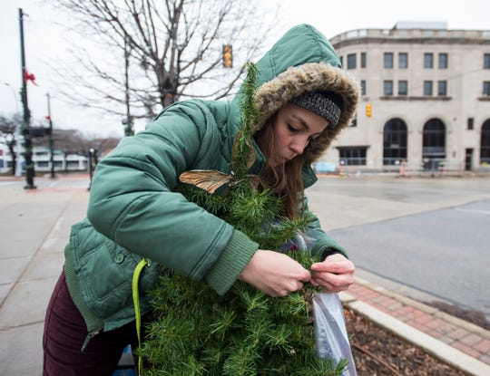 Times Herald reporter Jackie Smith hangs items on a Christmas tree on the corner of Water and Military streets Friday, Dec. 21, 2018 in downtown Port Huron.