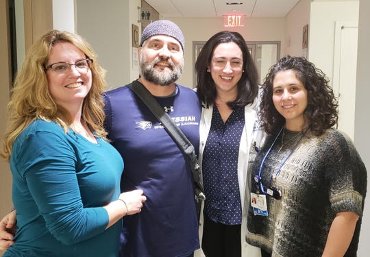 Eric Munson poses with his wife and medical staff at Memorial Sloan Kettering Cancer Center on Friday. From left: Michelle and Eric Munson, Dr. Jacqueline Stone and nurse Marie Petilli-Valentino.
