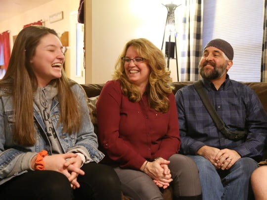 From left, Abbi, Micki, and Eric Munson laugh about a family memory at their home in Highland on December 20, 2018.  Eric discovered he had a brain tumor in January.