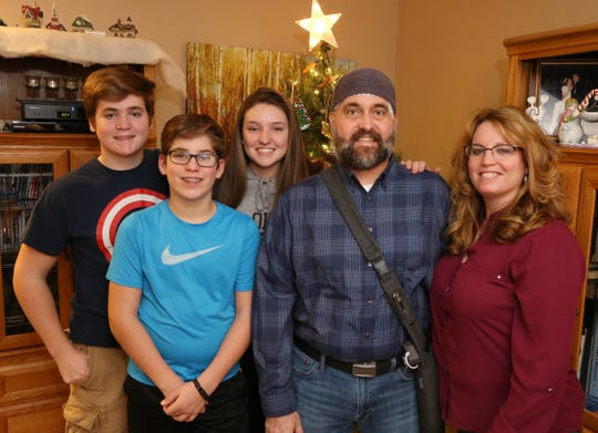The Munson family, from left, Luke, Joshua Yeaw, Abbi, Eric and Micki at their home in Highland on December 20, 2018.  Eric discovered he had a brain tumor in January.