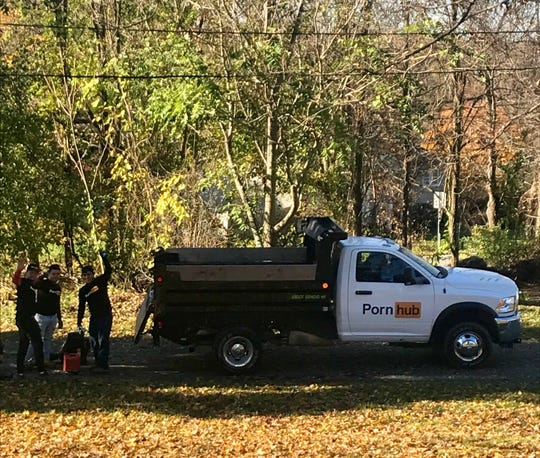 Workers from Dutchess Lawns sporting Pornhub T-shirts wave from the lawn of a Town of Poughkeepsie home.