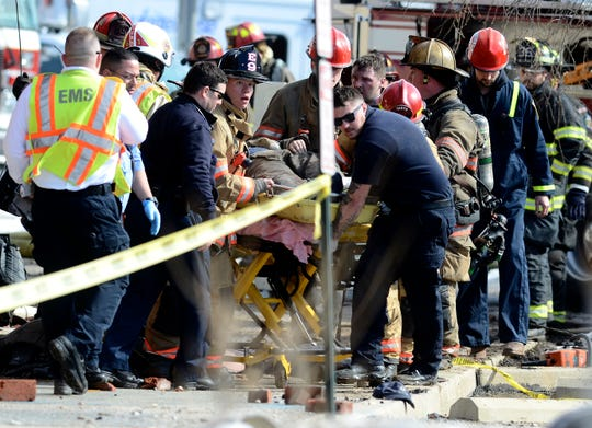 Emergency personnel move an injured firefighter to a waiting ambulance after a wall collapse at the scene of yesterdays N. Broad St. fire trapped and injured several firefighters.  At least three were transported from the scene by ambulance. John A. Pavoncello photo