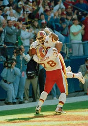 Washington Redskins tackle Tim Johnson (78) picks up teammate Darrell Green (28) after Green intercepted a pass from Arizona Cardinals quarterback Steve Beuerle and ran it back for a touchdown during the second quarter, Oct. 16, 1994 at Washington's RFK Stadium. (AP Photo/Denis Paquin)