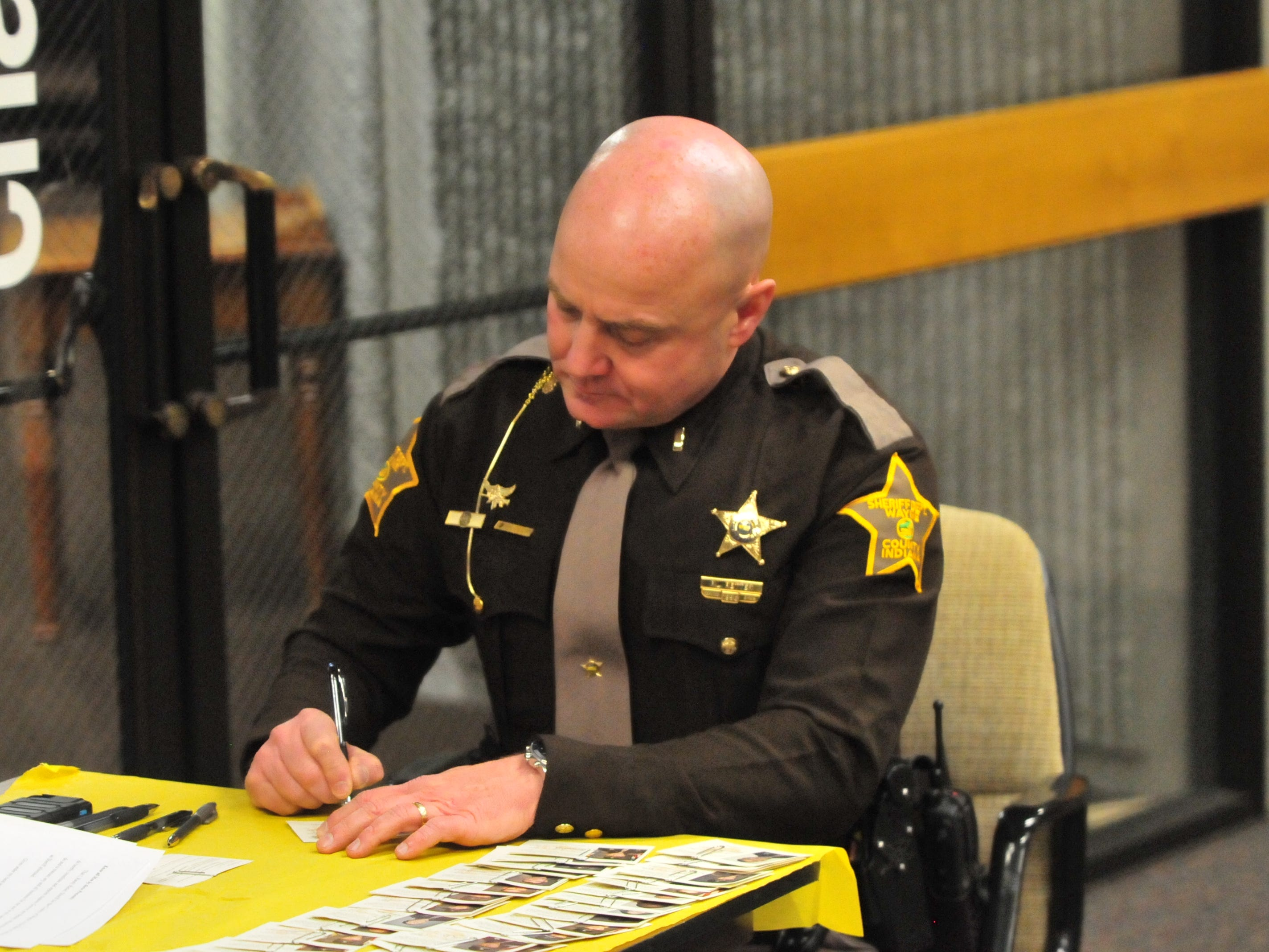 Lt. Randy Retter, the sheriff-elect, signs new identification cards for Wayne County Sheriff's Office personnel Friday after a swearing in ceremony.