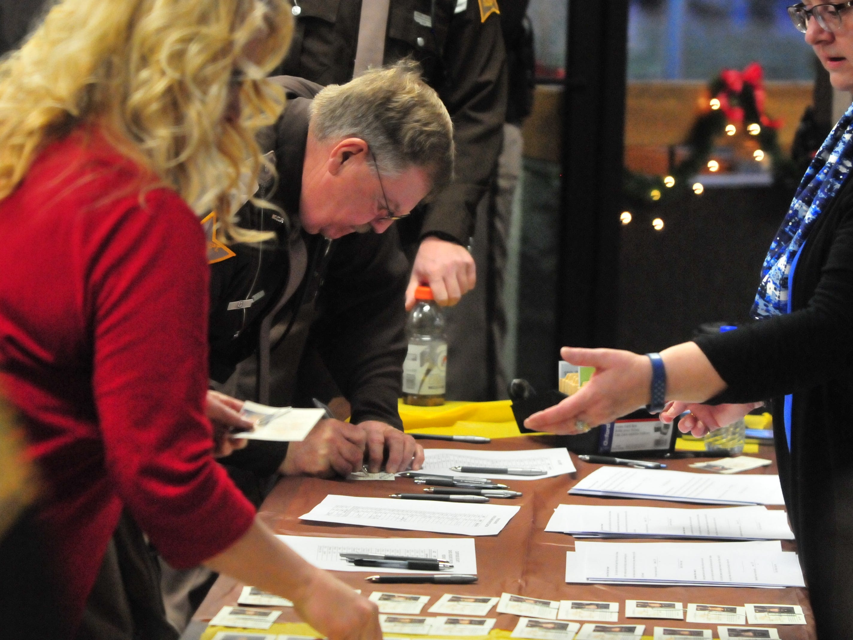 Wayne County Sheriff's Office personnel sign in and locate their new identification cards Friday at a group swearing in ceremony.
