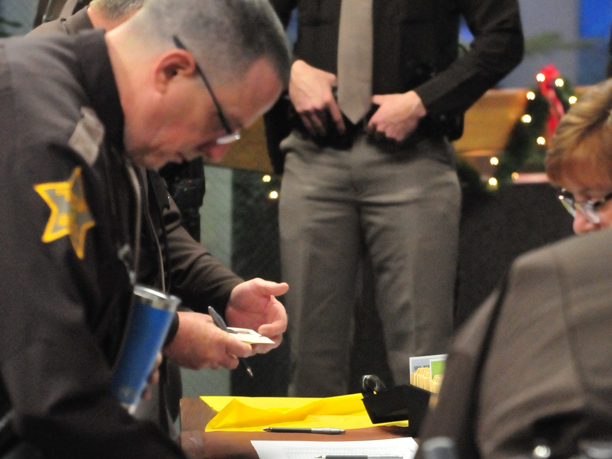 Wayne County Sheriff's Office personnel find their new identification cards that they needed to sign Friday at a group swearing in ceremony.