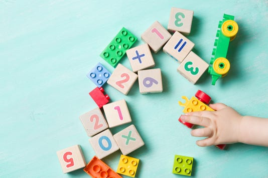 Child Playing With Wooden Cubes With Numbers And Colorful Toy Bricks On A Turquoise Wooden Background Toddler Learning Numbers Hand Of A Child Taking Toys