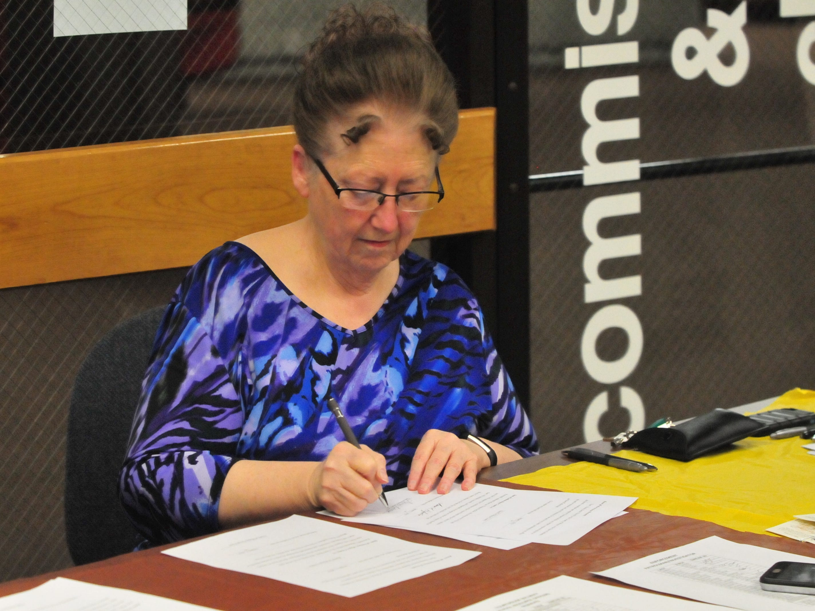 Wayne County Clerk Debra Berry signs paperwork Friday after swearing in Wayne County Sheriff's Office personnel