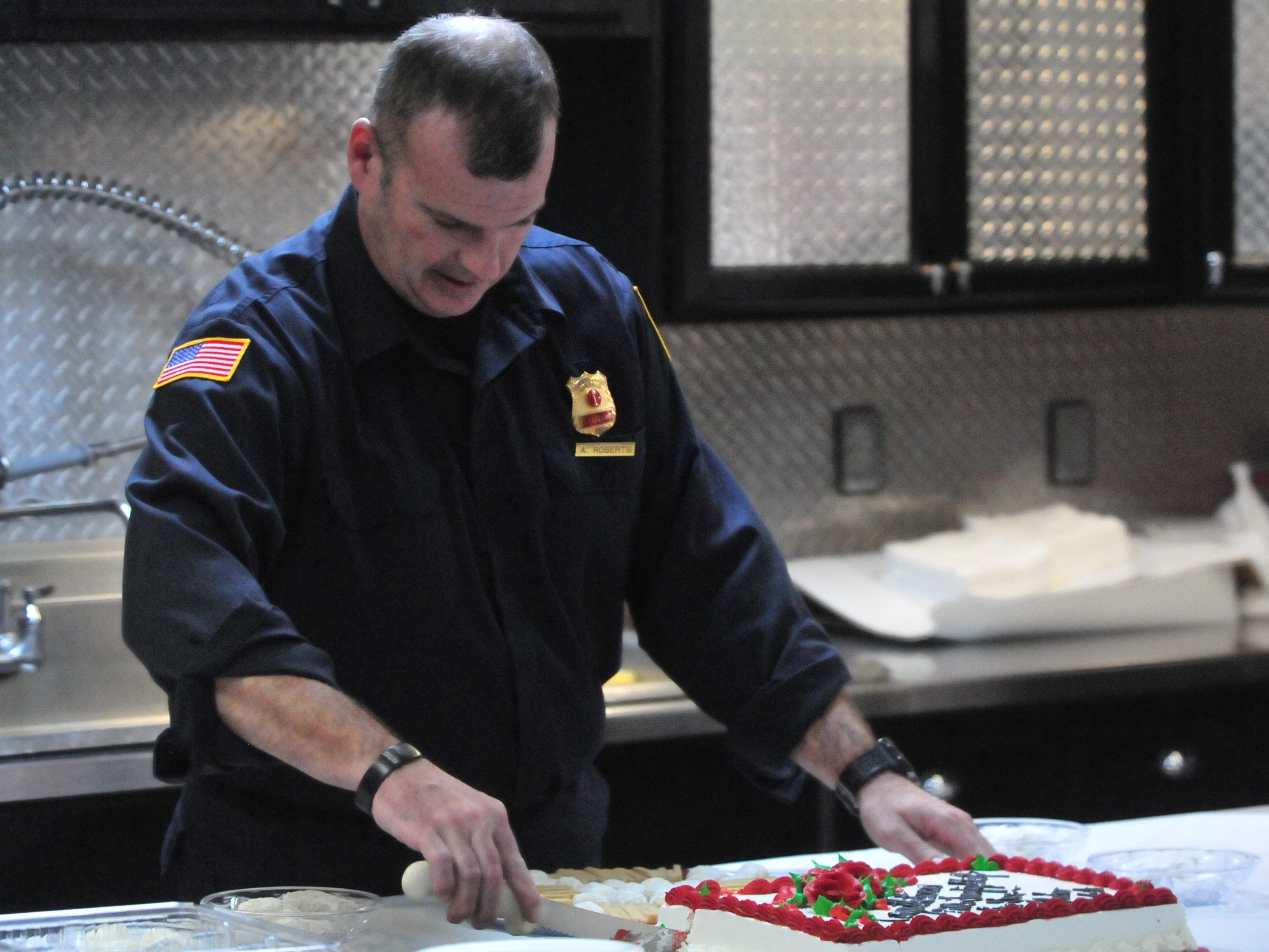 Lt. Andrew Roberts cuts a cake that honored him as Richmond Fire Department's Firefighter of the Year for 2018.
