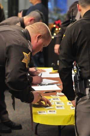 Wayne County Sheriff's Office personnel sign in and sign new identification cards Friday prior to a group swearing in ceremony.
