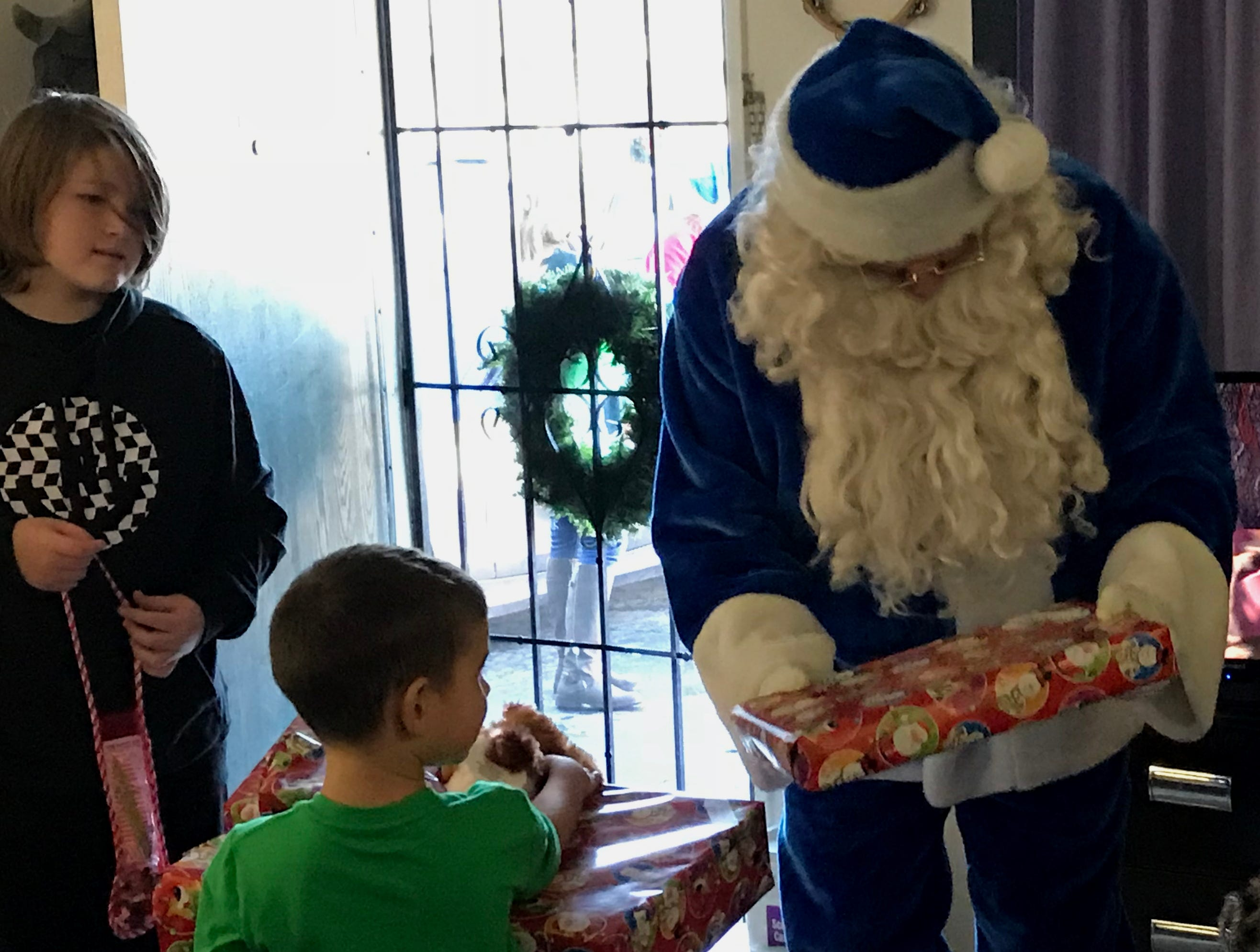 Blue Santa hands out Christmas gifts Friday to Oryn Yrigollen, 5, and his brother, Jacobs Rogers,11, at their Redding apartment.