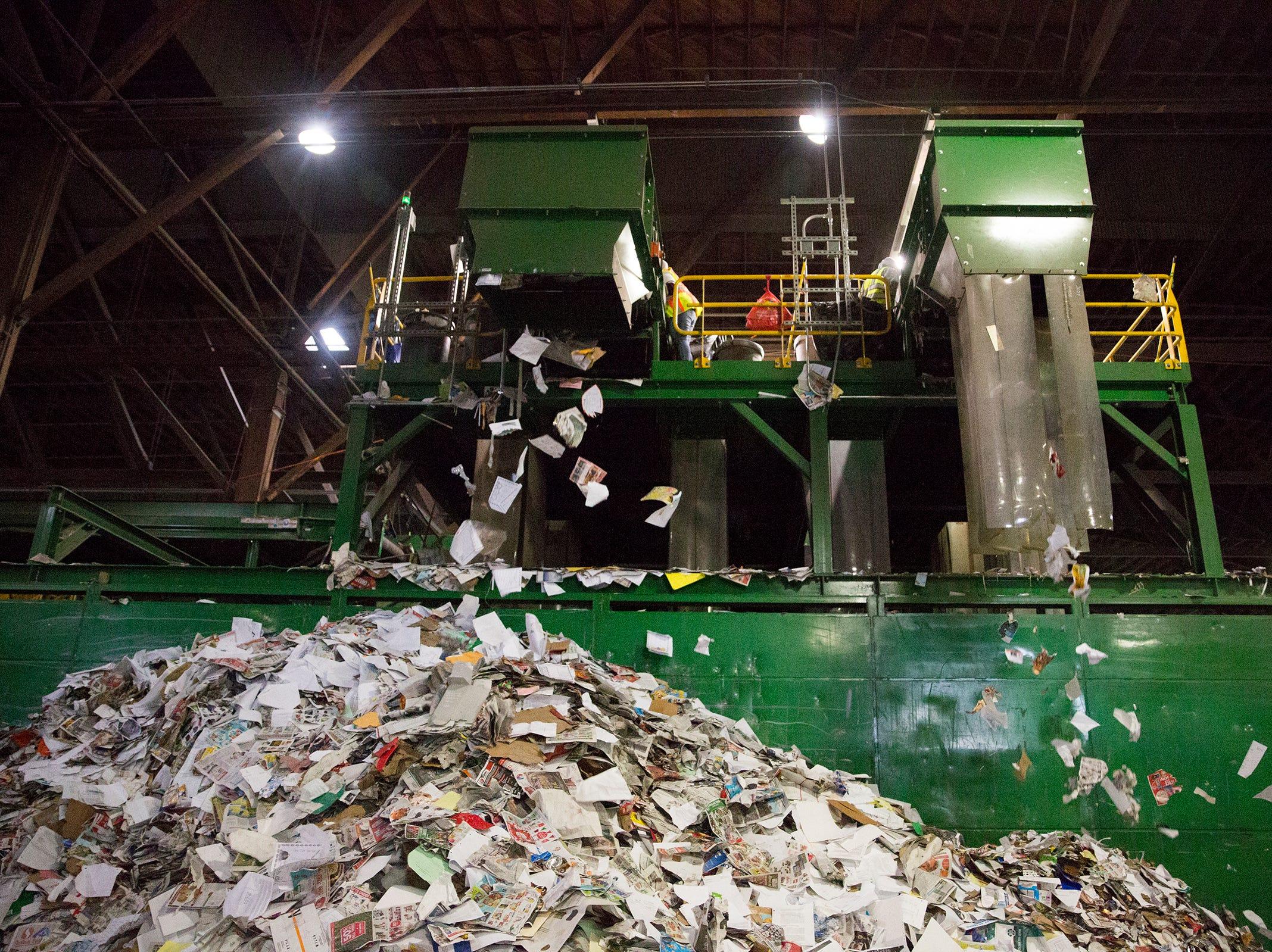 Paper falls at Garten Recycling in Salem on Thursday, Dec. 20, 2018.