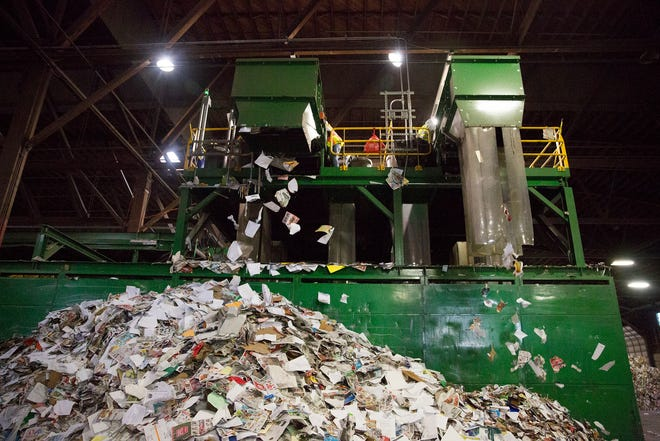 Paper falls at Garten Recycling in Salem on Thursday, Dec. 20, 2018.