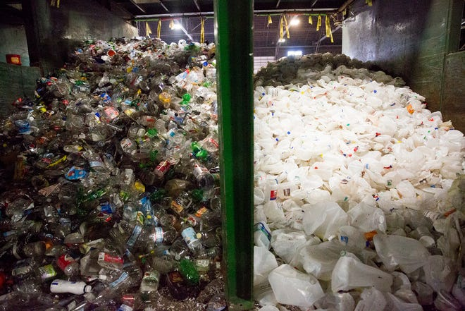 Recyclable milk jugs and plastic bottles are separated at Garten Recycling in Salem on Thursday, Dec. 20, 2018.